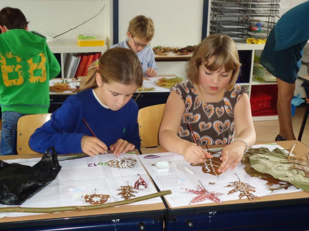 Het 4de leerjaar is kunstig bezig met herfstblaadjes.
